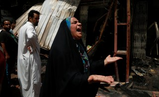 Image: A woman reacts at the scene of a car bomb attack in Baghdad
