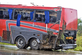 Image: A damaged OGA Charters bus is hauled away after a fatal rollover