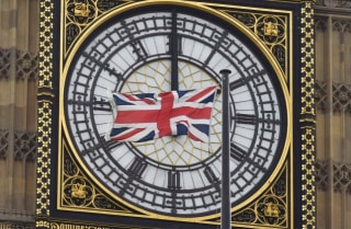 A British Union flag flutters in front of one of the clock faces of the 'Big Ben' clocktower of The Houses of Parliament in central London