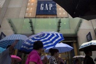 People carrying umbrellas pass by a Gap store on 5th avenue in midtown Manhattan in New York