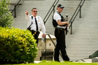 Image: A Secret Service agent orders people into buildings near the entrance to the West Wing