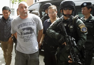 Image: Thai policemen escort an American suspect Hunter as he arrives at Don Mueang International Airport in Bangkok