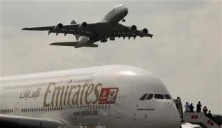 An Airbus A380 aircraft of Deutsche Lufthansa takes of passing over an Airbus A380 aircraft of Emirates at the ILA International Air Show in Schoenefeld south of Berlin