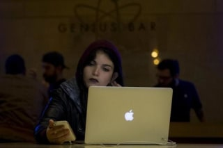 A customer uses an iPhone and a Macbook computer at the Genius Bar in the Apple Store at Grand Central Station in New York