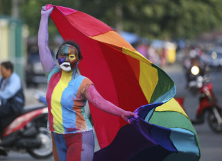 Image: An Indonesian activist with painted face and body waves a flag during a protest demanding LGBTQ equality