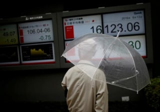 A man looks at an electronic board showing the recent exchange rate between Japanese yen against the U.S. dollar and Japan's Nikkei average outside a brokerage in Tokyo