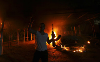 A protester reacts as the U.S. Consulate in Benghazi is seen in flames on September 11, 2012