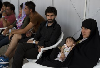 Image: Afghan migrants who live in the Hellenikon refugee and migrant camp register for asylum