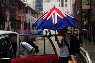 Image: A man closes his umbrella designed like the British flag