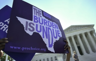 Image: An abortion rights activist holds placards outside of the Supreme Court