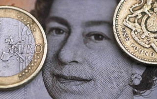 Photo illustration of a two Euro coin pictured next to a one Pound coin on top of a portrait of Britain's Queen Elizabeth