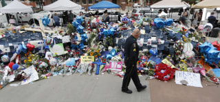 Image: A policeman visits a makeshift memorial at the Dallas police headquarters