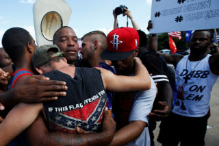 Image: People, including a man wearing a confederate flag, hug after taking part in a prayer circle after a Black Lives Matter protest following the multiple police shootings in Dallas