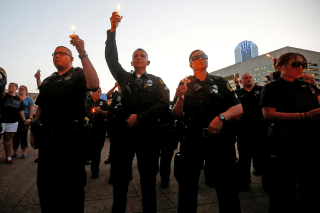 Image: Dallas police officers take part in a candlelight vigil at Dallas City Hall