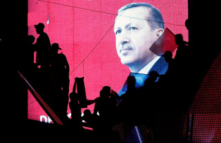 Image: Turkish Supporters are silhouetted against a screan showing President Tayyip Erdogan during a pro-government demonstration in Ankara