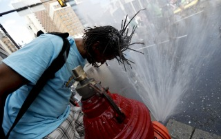 Image: A supporter of Sen. Bernie Sanders cools off during a march in downtown Philadelphia