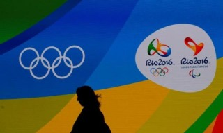 A journalist walks in front of a screen with olympics logos during the medal launching ceremony in Rio de Janeiro