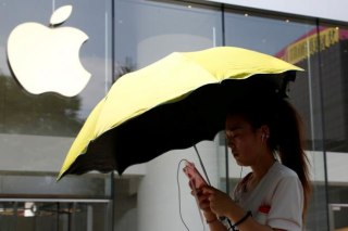 A woman uses a phone outside an Apple store in Beijing