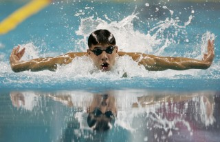 Syria's Anys swims to win his heat during the men's 100m butterfly swimming heats at the 15th Asian Games in Doha