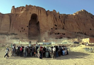 Image: Villagers stand in front of the remains of the giant Buddhas of Bamiyan