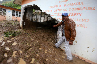 Image: Resident shows a classroom damaged by a mudslide following heavy showers caused by the passing of Tropical Storm Earl, in the town of Temazolapa