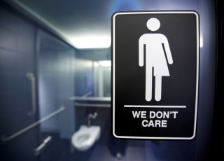 Image: A sign protesting a North Carolina law restricting transgender bathroom access is seen in the bathroom stalls
