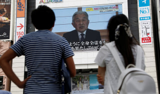 Image: People watch a large screen showing Japanese Emperor Akihito's video address in Tokyo