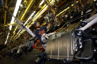 Jacob Bailey conducts assembly work on an SUV chassis at the General Motors Assembly Plant in Arlington, Texas