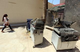 Image: An Iraqi woman walks past burnt incubators