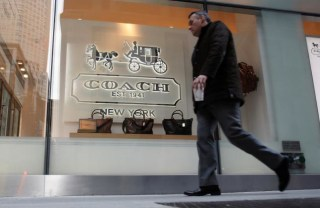 A man walks past a Coach store on Madison Avenue in New York