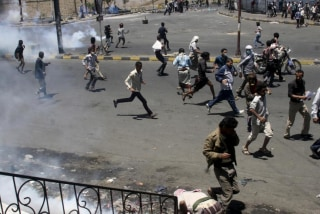 Anti-Houthi protesters seek refuge as pro-Houthi police troopers use tear gas to disperse them in Taiz