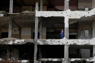 Image: A Palestinian girl stands on a floor of a damaged building in Gaza