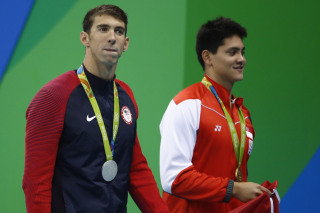Image: Silver medalist Michael Phelps waves next to gold medalist Joseph Schooling from Singapore after the Men's 100m Butterfly Final.