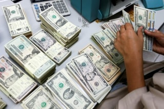 A bank employee counts U.S. dollar notes at a Kasikornbank in Bangkok