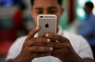 A salesman checks a customer's iPhone at a mobile phone store in New Delhi