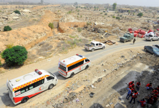 Image: A Syrian Arab Red Crescent convoy waits at the entrance of the besieged Damascus suburb of Daraya