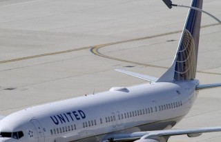 A United Airlines plane with the Continental Airlines logo on its tail, sits at a gate at O'Hare International airport in Chicago