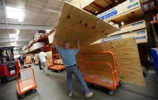 A man loads plywood to board up windows at a Home Depot store in Freeport on Long Island