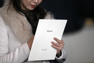 A woman clutches her resume at the Colorado Hospital Association health care career fair in Denver