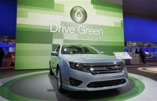 "The 2010 Ford Fusion is seen in front of a sign that reads ""Drive Green"" at the 2010 North American International Auto Show during press days in Detroit, Michigan"