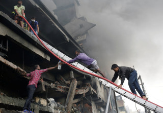 Image: People try to extinguish a fire at a garment packaging factory outside Dhaka, Saturday.