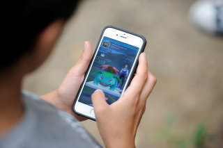 Image: A boy plays Pokemon Go