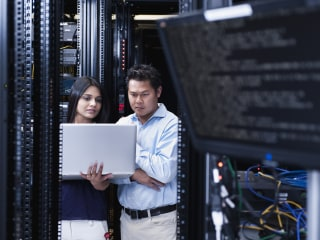 Business people using laptop in server room