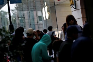 Image: Customers wait for the release of Apple's new iPhone 7 in Tokyo.