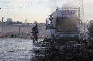 Image: A boy rides a bicycle near a damaged aid truck after an airstrike on the rebel held Urm al-Kubra town