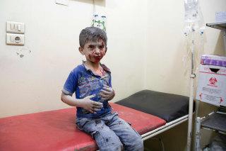 Image: A Syrian boy awaits treatment at a make-shift hospital in Aleppo Saturday.
