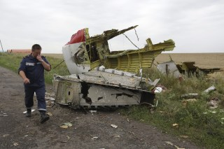 Image: A Ukrainian rescue worker passes wreckage of Malaysia Arilines flight MH17, which was brought down by a missile on July 14, 2014.