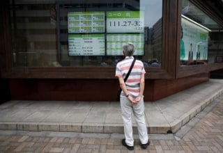 A man looks at an electronic board showing the Japanese yen's exchange rate against Euro outside a brokerage in Tokyo, Japan