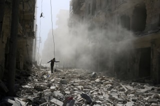 Image: A man walks on the rubble of damaged buildings after an airstrike on the rebel held al-Qaterji neighbourhood of Aleppo