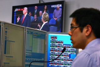 A trader works at his desk as the US presidential town hall debate is shown on television at Citibank's trading floor located in central Sydney, Australia